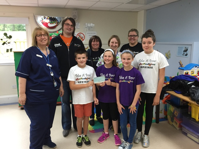 Take a bow theatre company present a cheque to the staff at the children's ward